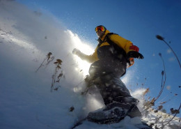 Jeremy Jensen surfing thru the snow and weeds without any bindings on his Grassroots Powsurfer