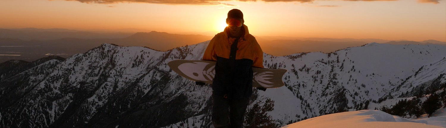 Jeremy Jensen hiking in the sunset with his Grassroots Barracuda 3 Dimensional base powsurfer.
